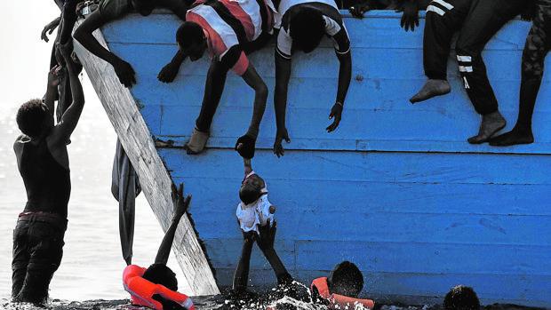 Emigrantes intentan sacar a un bebé del agua, mientras esperan a ser rescatados en el Mediterráneo