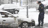 Un policía toma nota ante un vehículo calcinado durante unos disturbios en el suburbio de Rinkeby, este lunes en Estoc