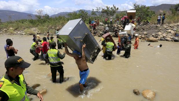 Venezolanos cruzan la frontera con Colombia por el río Táchira cargados de enseres