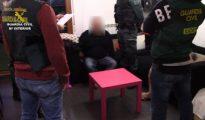 Los agentes custodian a uno de los tres detenidos