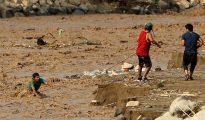 Ciudadanos intentan cruzar el río rímac, en el distrito de Huachipa (Lima), luego de la caída de un puente