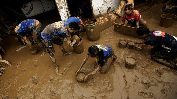 Voluntarios limpian una casa inundada tras un deslizamiento