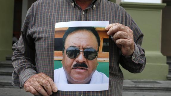 Un compañero de Ricardo Monlui Cabrera sostiene su retrato.