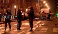 Un policía observa cómo se retira un vehículo destruido por vándalos en un suburbio parisino el 13 de febrero de 2017. (Imagen tomada de un vídeo de Ruptly).