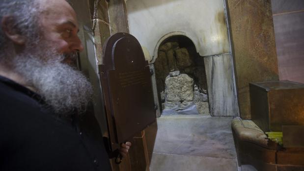 Un clérigo griego ortodoxo, fotografiado delante de la tumba de Jesucristo, en la Iglesia de la Santa Sepultura