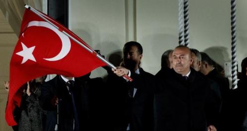 El ministro de Exteriores turco, Mevlut Cavusoglu (C), ondea la bandera turca ante seguidores del Gobierno de ese país, en los jardines del Consulado de Turquía en Hamburgo