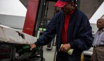 Un venezolano llena el depósito de combustible en una gasolinera de Caracas