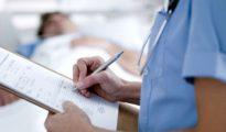 Una enfermera toma nota de los datos de un paciente en un hospital.