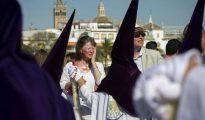 Unos turistas se protegen del sol con crema al paso de los nazarenos de la Hermandad de La Estrella, en el puente de Triana en Sevilla, ayer Domingo de Ramos