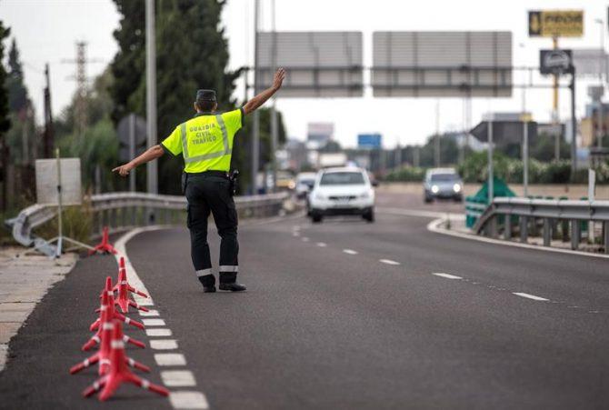 Un agente de la Guardia Civil de Tráfico da el alto a un conductor en un control.