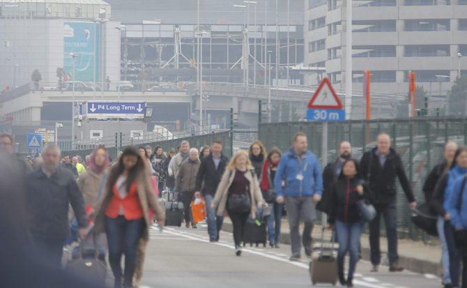 Los pasajeros evacúan la zona aeroportuaria tras registrarse explosiones en el aeropuerto internacional de Zaventem, cerca de Bruselas.