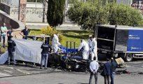 La policía forense cubre un cadáver sacado de la caravana donde murieron tres hermanas gitanas, en Roma