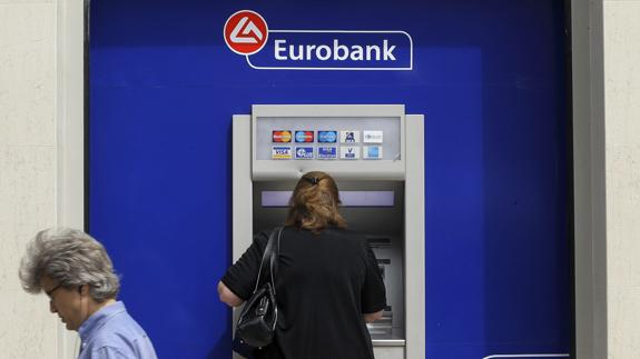 Una mujer utiliza un cajero de Eurobank en Atenas, Grecia.