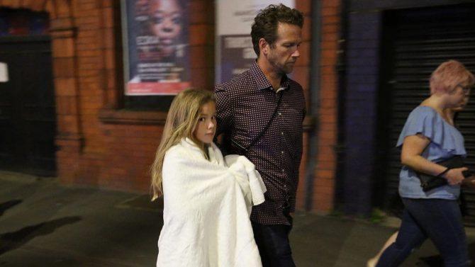 Un padre acompaña a su hija luego de las explosiones en el recital de Ariana Grande en Manchester