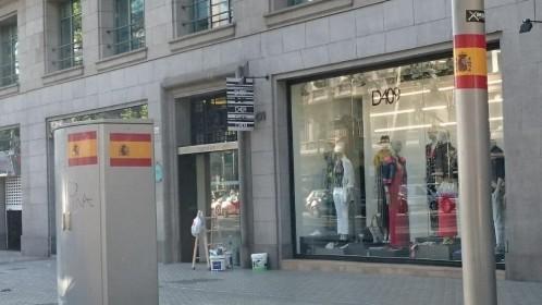 Centenares de grandes pegatinas que reproducen la bandera española han aparecido esta mañana en elementos del mobiliario urbano y en edificios de Barcelona