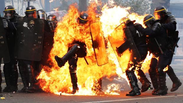 Policías franceses antidisturbios envueltos en llamas durante los enfrentamiento de París por el Primero de Mayo