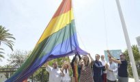 Autoridades locales despliegan una gran bandera con los colores arcoiris.