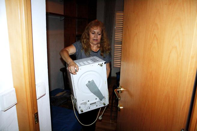 Aurora González con el microondas que tiene guardado en su dormitorio para que no se lo roben (La Vanguardia)