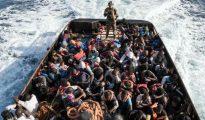 Un guardacostas libio, en pie a bordo de un bote durante el rescate de 147 ilegales que se dirigían a Europa