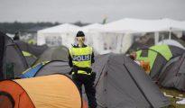 Una policía sueca vigila el lugar donde acampan muchos de los jóvenes asistentes al festival de música.