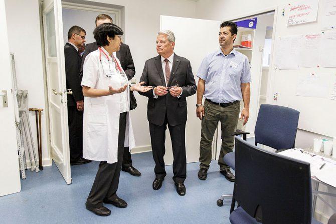 El presidente de Alemania, Joachim Gauck, conversa con un grupo de médicos en la enfermería de un centro de acogida de inmigrantes en Berlin-Wilmersdorf, el 26 de agosto de 2015. (Foto: Jesco Denzel/Bundesregierung vía Getty Images).