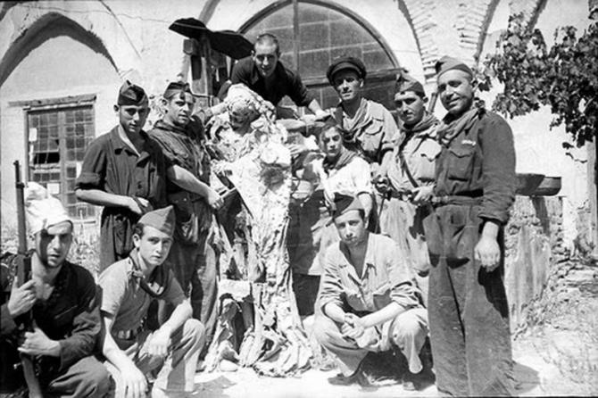 Combatientes comunistas posando con la momia de un sacerdote.
