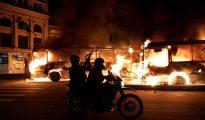 Policías antidisturbios pasan frente a unos autobuses en llamas en Rio de Janeiro