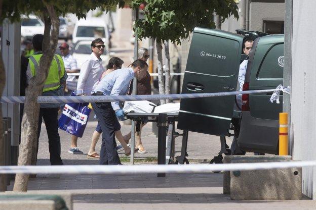 Empleados del retén fúnebre trasladan el cuerpo del hombre asesinado, ayer, en la calle Estatut de Benicàssim.