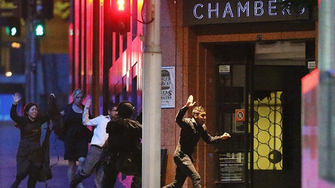 Un grupo de personas huye con las manos arriba del café Lindt durante una toma de rehenes en Sídney, Australia, el 16 de diciembre de 2014.