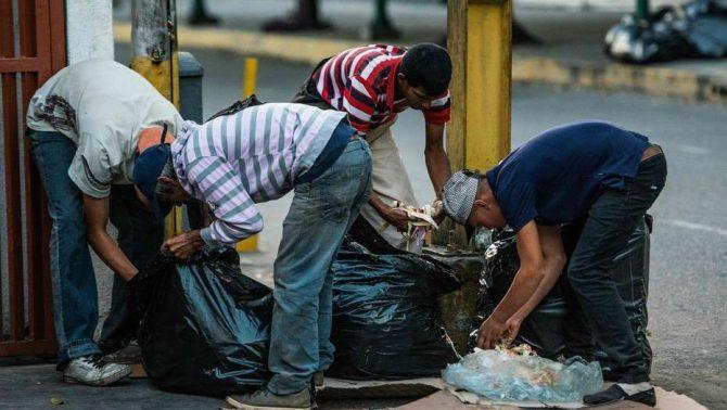 Un grupo de personas hurga la basura en busca de comida en las calles de Caracas.