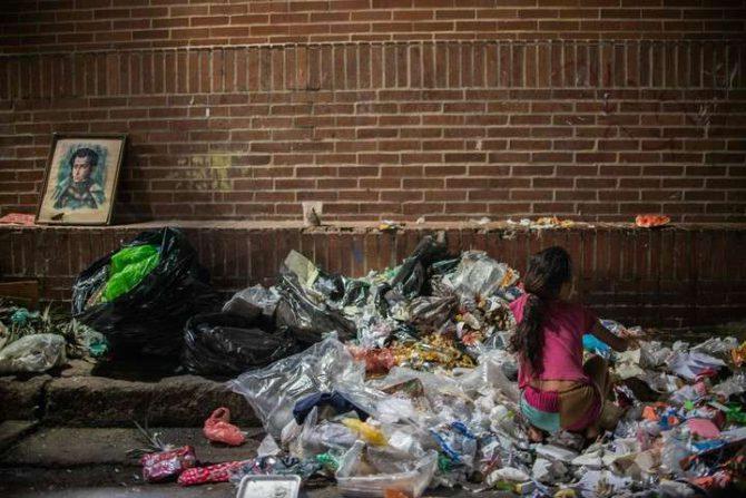 Una nina busca algo que comer entre la basura en Caracas.