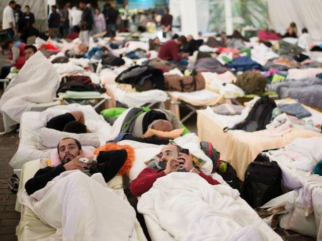 Los refugiados descansan en sus camas en un refugio temporal para solicitantes de asilo en el recinto de un festival local de eventos en Wiesen, Austria, a unos 70 kilómetros de la frontera entre Hungría y Austria, el 13 de septiembre de 2015.