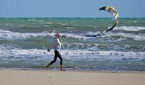 Una mujer camina por una playa de Rímini