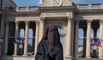 Una mujer cubierta con el niqab posa frente a la Asamblea Nacional francesa.