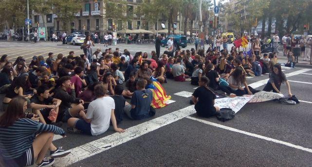 Estudiantes se sientan en la calzada de la Gran Vía de Barcelona para cortar el tráfico.
