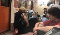 Varios viajeros se protegen agachados en el Metro de Madrid