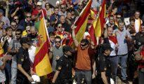 Un grupo de personas con banderas españolas aplauden a los agentes de la Policía Nacional en la entrada al pabellón Siglo XXI de Zaragoza, donde tiuvo lugar la asamblea de cargos públicos que organizó Podemos a favor del referéndum.