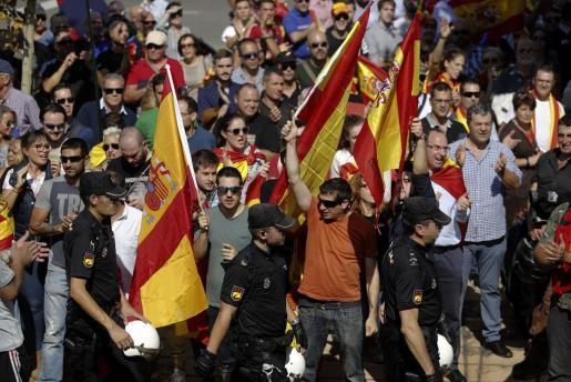 Un grupo de personas con banderas españolas aplauden a los agentes de la Policía Nacional en la entrada al pabellón Siglo XXI de Zaragoza, donde tiene lugar la asamblea de cargos públicos que ha organizado el grupo confederal de Unidos Podemos en el Congreso.