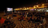 Jóvenes ven una película en una playa de Marsella