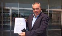 Armando Robles muestra la denuncia en las puertas de la Ciudad de la Justicia de Málaga.