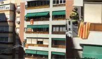 Un bombero durante la intervención en el balcón, con la estelada colgada