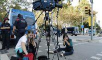 Una periodista del canal de televisión Bloomberg, se maquilla antes de contactar en directo desde la entrada principal al parque de la Ciutadella de Barcelona
