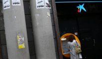 Una persona retira dinero de un cajero de CaixaBank, hoy en Barcelona