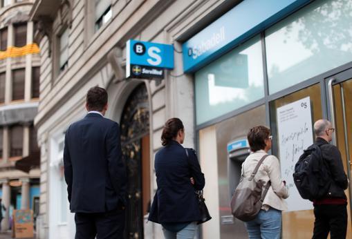 Cuatro personas hace cola en un cajero de Banc Sabadell