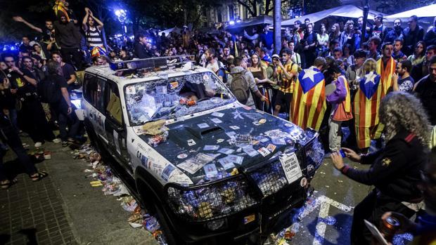 Imagen de un coche de la Guardia Civil destrozado en Barcelona