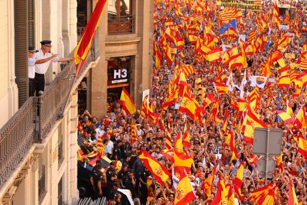 Dos mandos de la policía española observa el paso de los manifestantes defensores de la unidad nacional.