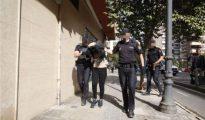 Los policías trasladan a la detenida por la muerte de su marido en una casa de Valencia.