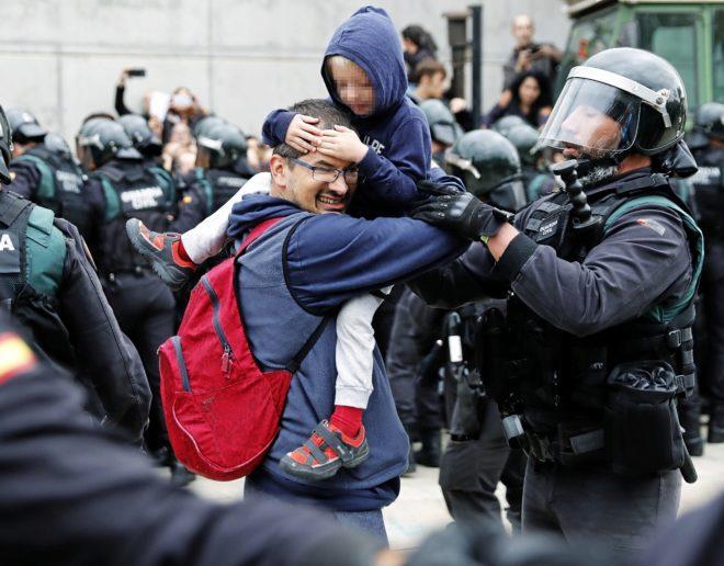 Un guardia civil trata cuidadosamente de que un padre saque a su hijo de un tumulto, ayer, en Sant Julià de Ramis (Gerona).
