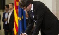 El presidente de la Generalitat, Carles Puigdemont, firma el documento sobre la Independencia después de comparecer ante el pleno del Parlament