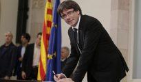 El president Puigdemont firmando la declaración (AP)